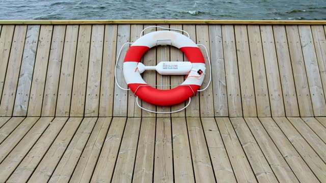 life belt hanging on wooden pier or boat at midday - life belt stock videos & royalty-free footage