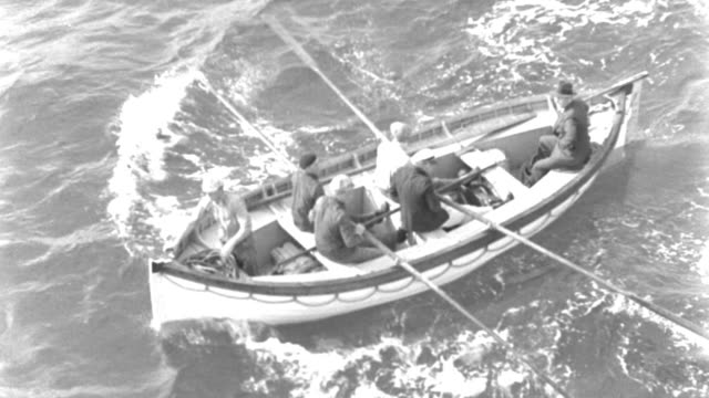 a life boat containing four men sailing on an ocean. - oar stock videos & royalty-free footage