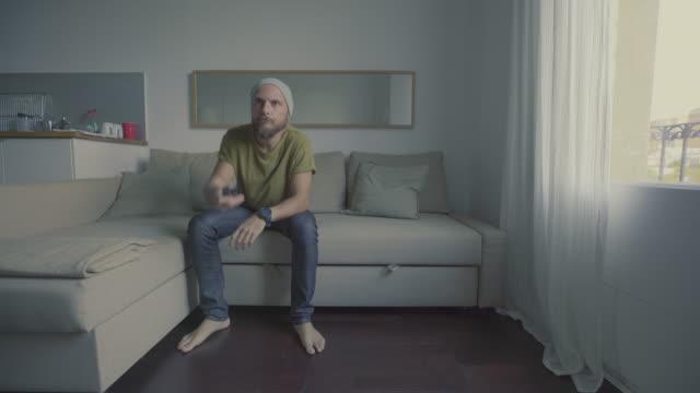 vídeos y material grabado en eventos de stock de vida durante el encierro de pandemia covid-19: hombre en cuarentena en casa - cambiar de canal