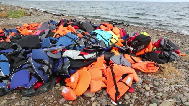 life jackets abandoned on the beach by syrian migrants after they arrived from turkey on the greek island of lesvos. - isil konflikt stock-videos und b-roll-filmmaterial