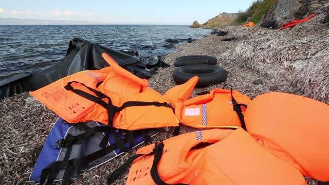 vídeos y material grabado en eventos de stock de life jackets and remains of boats left by syrian migrants fleeing the war and escaping to europe, landing on the greek island of lesvos on the north coast at efthalou. up to 4,000 migrants a day are landing on the island and overwhelming the authorities. t - chaleco salvavidas