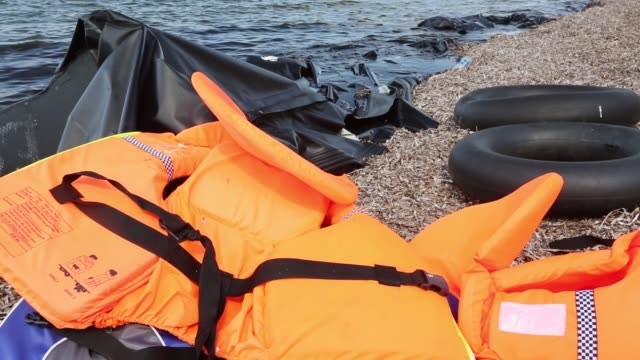 life jackets and remains of boats left by syrian migrants fleeing the war and escaping to europe, landing on the greek island of lesvos on the north coast at efthalou. up to 4,000 migrants a day are landing on the island and overwhelming the authorities. t - life jacket stock videos & royalty-free footage