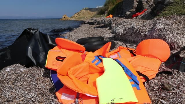 life jackets and remains of boats left by syrian migrants fleeing the war and escaping to europe, landing on the greek island of lesvos on the north coast at efthalou. up to 4,000 migrants a day are landing on the island and overwhelming the authorities. t - undocumented immigrant stock videos & royalty-free footage