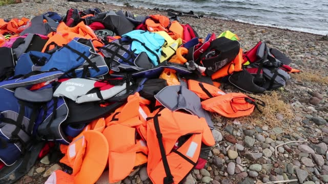 Life jackets and remains of boats left by Syrian migrants fleeing the war and escaping to Europe, landing on the Greek island of Lesvos on the north coast at Efthalou. Up to 4,000 migrants a day are landing on the island and overwhelming the authorities. T