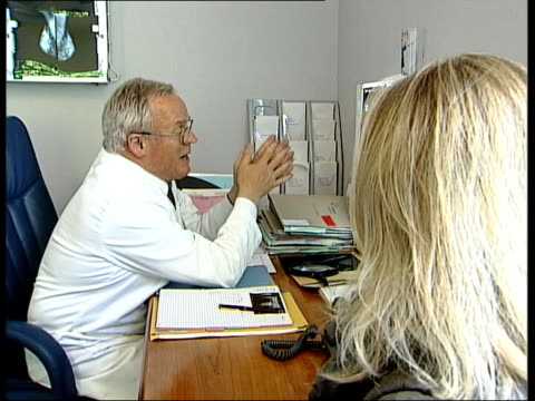 breast cancer doctors consultation england london int woman patient sat in room with doctor as he looks at mammograms on lightbox on his desk and... - lightbox stock videos & royalty-free footage