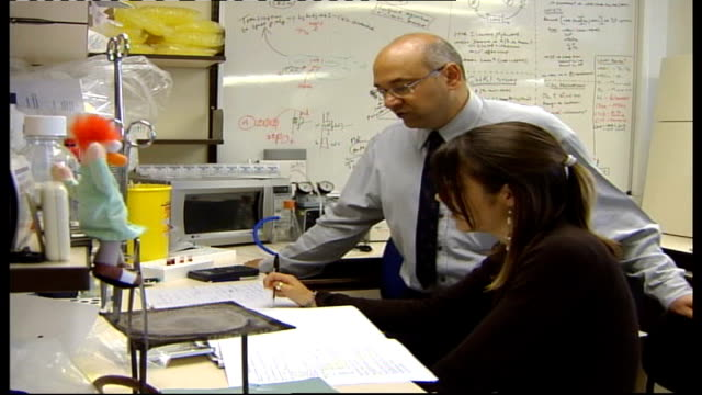 Cystic Fibrosis INT Dr Anil Mehta standing next to a seated woman in science laboratory DISSOLVE TO