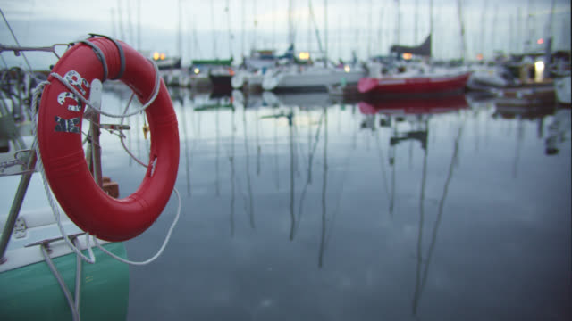a life preserver ring hangs on the side of a sailboat in a harbor in puget sound near seattle, washington - inlet stock videos & royalty-free footage