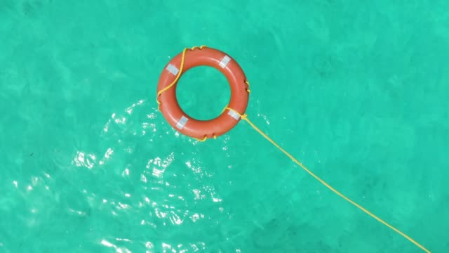 life rescue buoy in tropical water aerial - help single word stock videos and b-roll footage