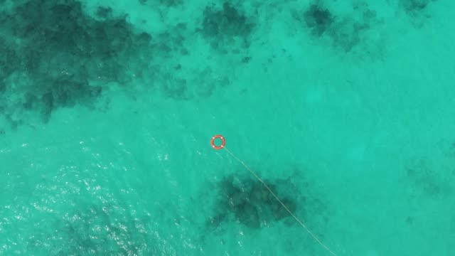 life rescue buoy in tropical water aerial - buoy stock videos & royalty-free footage