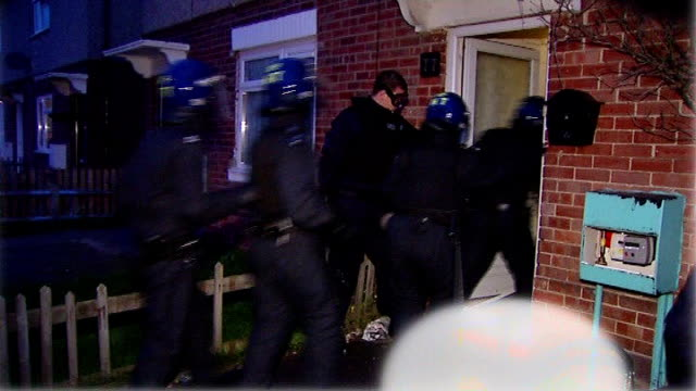 life sentences for traffickers in new slavery bill t24010833 / tx slough photography** police officers dressed in riot gear raiding a house where... - リチャード・パロット点の映像素材/bロール