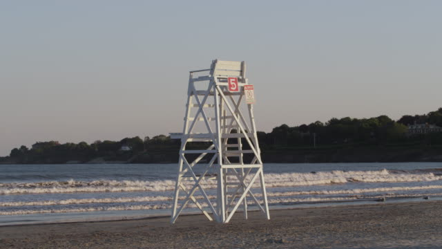 lifeguard chair on the beach at newport rode island at sunset. - lifeguard chair stock videos & royalty-free footage