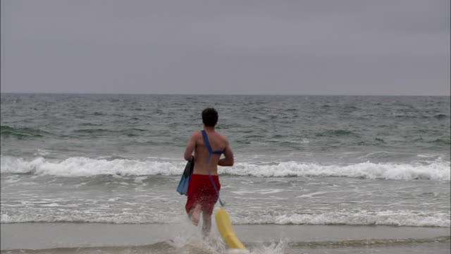 stockvideo's en b-roll-footage met a lifeguard charges into the ocean. - badmeester