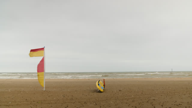 lifeguard flag and board on beach - coastline stock videos & royalty-free footage