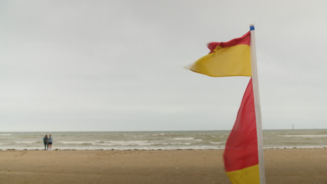 stockvideo's en b-roll-footage met lifeguard flag blows in wind on overcast day - badmeester
