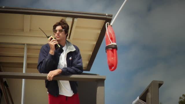 vídeos y material grabado en eventos de stock de ms la lifeguard holding walkie-talkie then picking up mobile phone looking around standing at lifeguard station, laguna beach, california, usa - vigilante