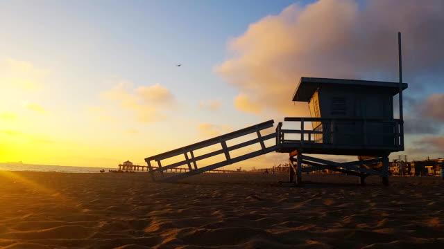 lifeguard hut and pier  at sunset in manhattan beach - cabina del guardaspiaggia video stock e b–roll