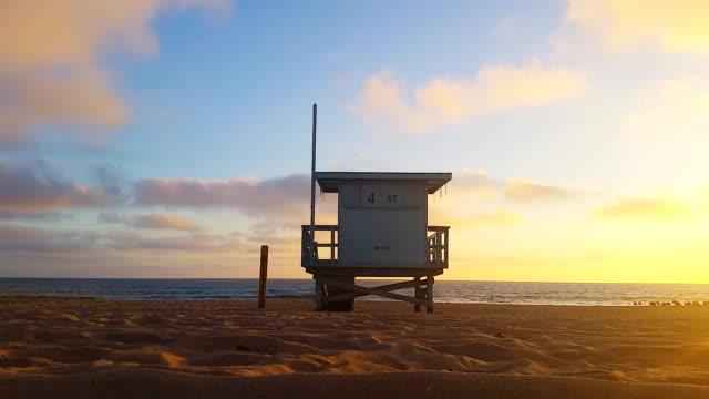 lifeguard hut at sunset in southern california beach - cabina del guardaspiaggia video stock e b–roll