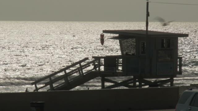 MS Lifeguard hut with ocean reflecting sun at dusk in background, Malibu, California, USA