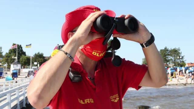 vidéos et rushes de a lifeguard is using binoculars to watch the beach and ensure the safety of people refreshing themselves in the ocean at high summer temperatures... - chapeau de soleil