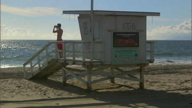 ws lifeguard looking through binoculars and using bullhorn outside lifeguard hut / vista del mar, california, usa - binoculars stock videos & royalty-free footage