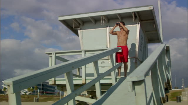 la ws lifeguard looking through binoculars outside lifeguard hut / vista del mar, california, usa - binoculars stock videos & royalty-free footage