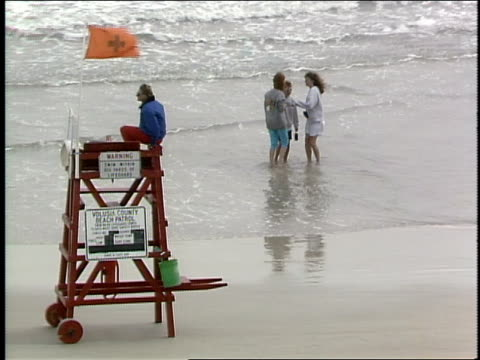 lifeguard on chair and kids playing on beach in daytona, florida - lifeguard chair stock videos & royalty-free footage