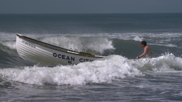 a lifeguard pushes a wooden rescue boat into the ocean.  the waves crash over the boat and he fights with the surf. - bagnino video stock e b–roll