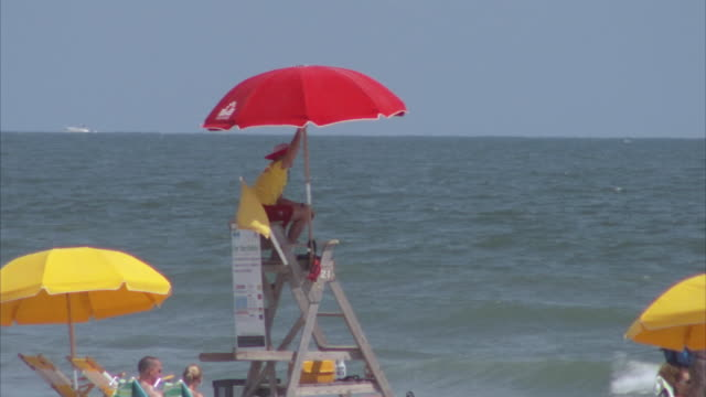 ms lifeguard sitting in elevated seat at the beach / folly beach, south carolina, united states - carolina beach stock videos & royalty-free footage