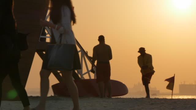 vídeos y material grabado en eventos de stock de lifeguard station and atlantis hotel from jumeirah beach at sunset, dubai, united arab emirates, middle east, asia - bañador de natación