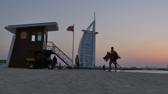 lifeguard station and burj al arab hotel from jumeirah beach at dusk, dubai, united arab emirates, middle east, asia - bagnino video stock e b–roll