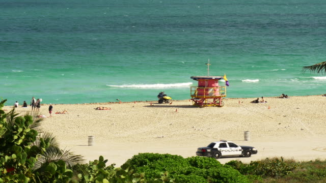 lifeguard tower in miami beach, south beach. police car and trucks passing by on the beach - spoonfilm stock-videos und b-roll-filmmaterial