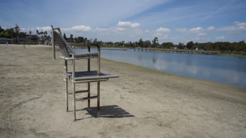 lifeguard tower overlooks an empty park as california gov. gavin newsom directed all californians to stay at home and maintain safe distances from... - long beach california video stock e b–roll