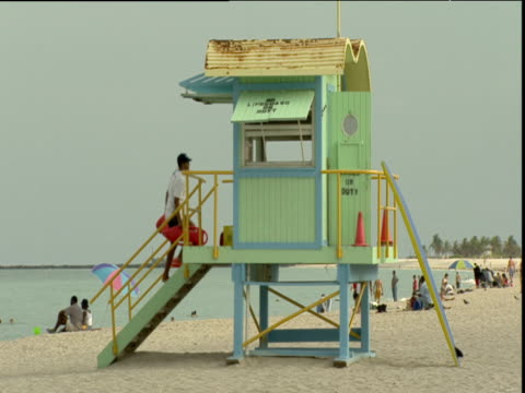 lifeguard walks up stairs and into lifeguard tower on beach miami - cabina del guardaspiaggia video stock e b–roll