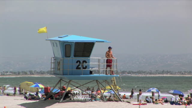 ms lifeguard watching people relaxing on beach from lifeguard tower, san diego, california, usa - bagnino video stock e b–roll