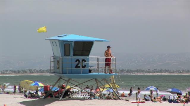 vídeos y material grabado en eventos de stock de ms lifeguard watching people relaxing on beach from lifeguard tower, san diego, california, usa - vigilante