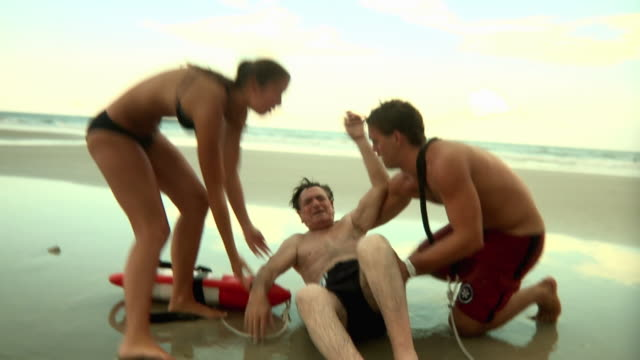 MS PAN ZI Lifeguards laying man on ground and checking pulse / Jacksonville, Florida, USA