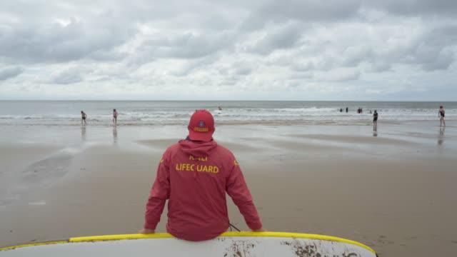 vídeos y material grabado en eventos de stock de rnli lifeguards on the beach. - vigilante