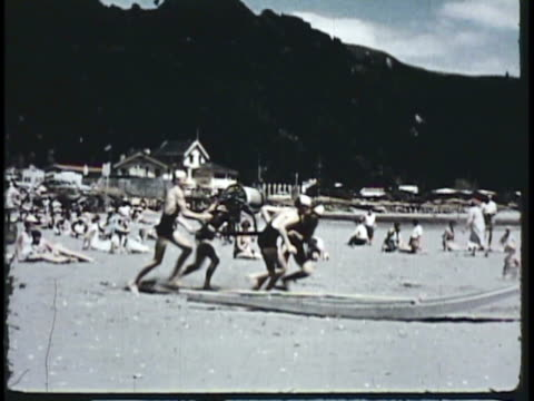 1955 montage ws pan ms lifeguards running with surfboards on beach, practicing / new zealand / audio - 1950 stock videos & royalty-free footage