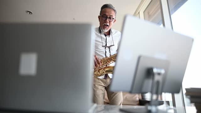 lifehack asiatisk aktiv senior man artist spelar saxofon och visar den för sin student med bärbar dator i vardagsrummet - människofinger bildbanksvideor och videomaterial från bakom kulisserna