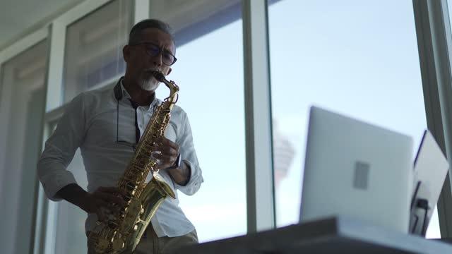 lifehack asian active senior man artist playing saxophone and showing it to his student using laptop in living room - menara kuala lumpur tower stock videos & royalty-free footage