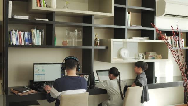 ライフハックアジアの中国人の父親は、彼の横にデジタルタブレットを使用して彼の同僚のコワーキングとヘッドセットのビデオ通話で自宅で働いています - 本棚点の映像素材/bロール