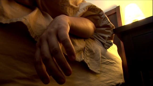 a lifeless hand hangs over the edge of a bed. - violence stock videos & royalty-free footage