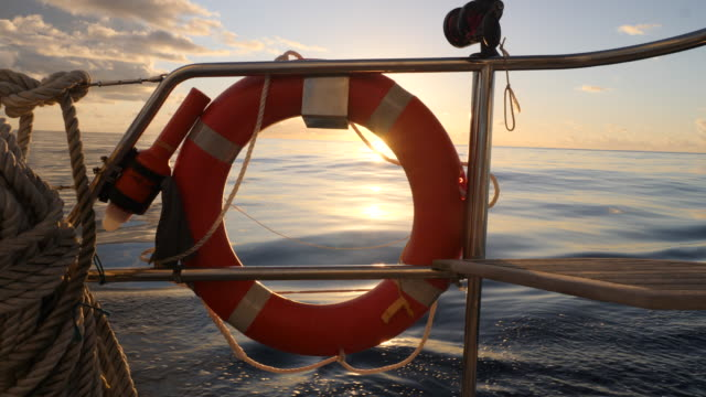 vídeos de stock e filmes b-roll de a lifesaver flotation device on a sailboat boating at sunset. - slow motion - boia equipamento de desporto aquático