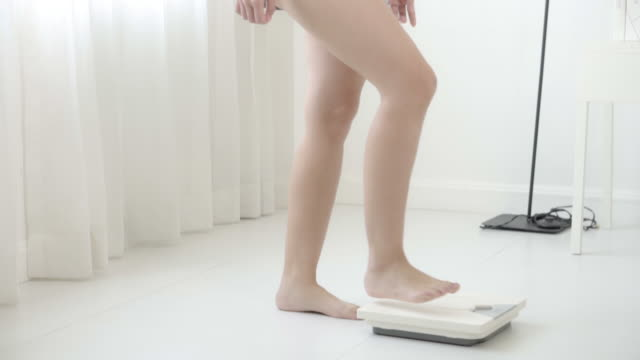 lifestyle activity with leg of woman walking measuring weight scale for diet, closeup feet of girl slim weighing measuring for food control, healthy care and wellbeing concept.