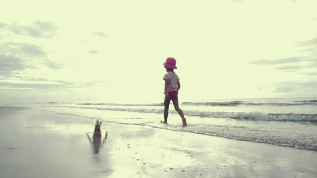lifestyle cinemagraph : baby girl walking on beach - shadow stock videos & royalty-free footage