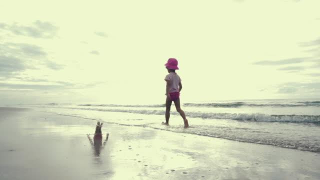 stockvideo's en b-roll-footage met lifestyle cinemagraph: meisje van de baby wandelen op strand - schaduw