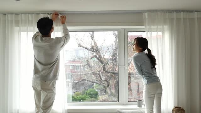 vídeos y material grabado en eventos de stock de lifestyle - couple hanging curtain at home - encuadre de tres cuartos