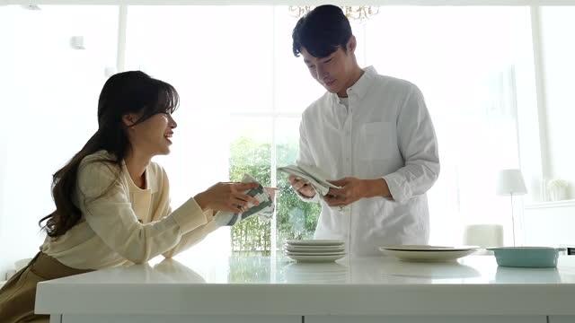 vídeos y material grabado en eventos de stock de lifestyle - couple polishing plates by towel in kitchen - trapo de limpiar el polvo
