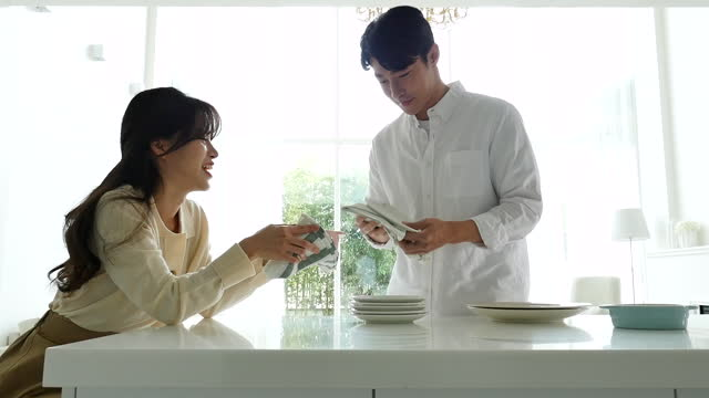 lifestyle - couple polishing plates by towel in kitchen - lappen reinigungsgeräte stock-videos und b-roll-filmmaterial