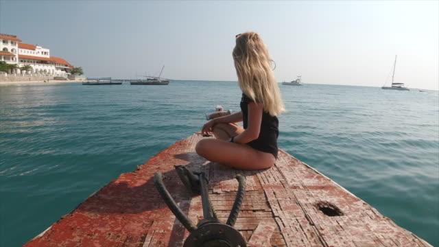 lifestyle of a woman sitting on a rough boat traveling to an island. - tropical climate stock videos & royalty-free footage